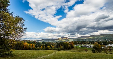 A photograph of trees turning fall colors. Clouds in the sky and hills in the background.