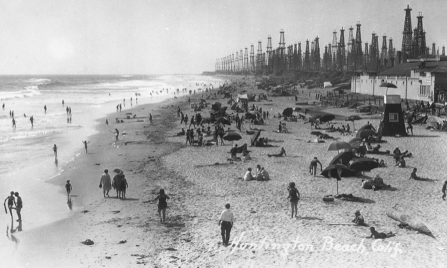 A black and white photograph of people on a beach, with oil derricks in the background.