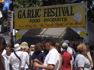 """A photo of a banner reading """"Garlic Festival Food Products, from Gilroy, CA, the Garlic Capital of the World"""". People are underneath the banner."""
